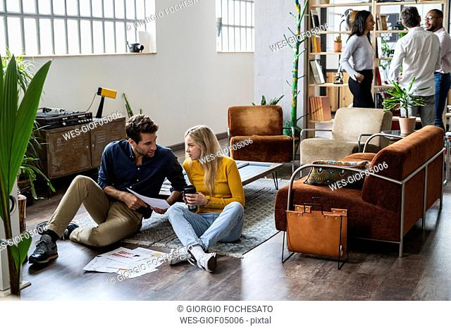 Businessman and businesswoman discussing documents in loft office