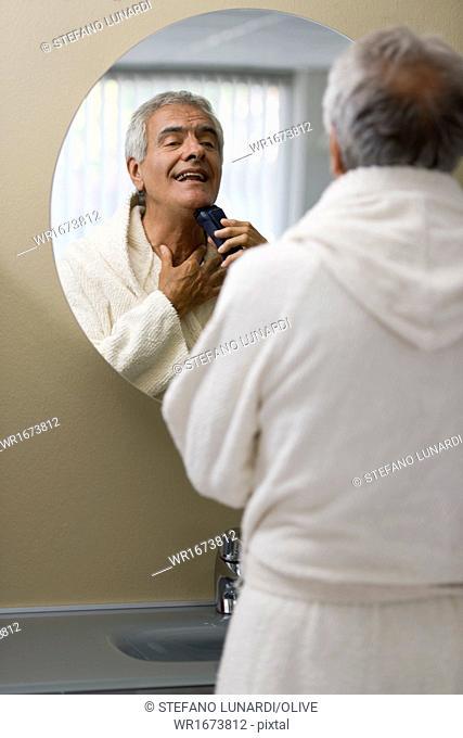 Mature man shaving in bathroom mirror