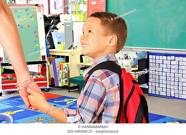 Five year old boy holding his mother's hand on the first day of school
