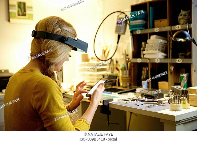 Female jewellery maker using smartphone touchscreen in design studio
