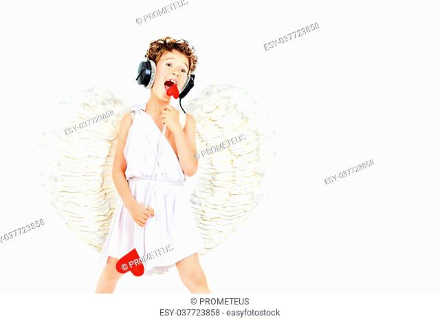 Cheerful little boy in a costume of angel listening to music in headphones and singing. Cupid. Valentine's day