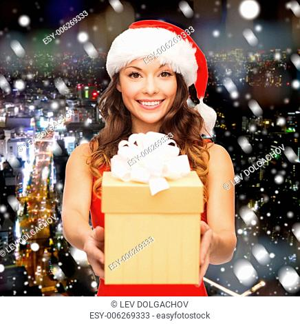 christmas, winter, happiness, holidays and people concept- smiling woman in santa helper hat with gift box over snowy night city background