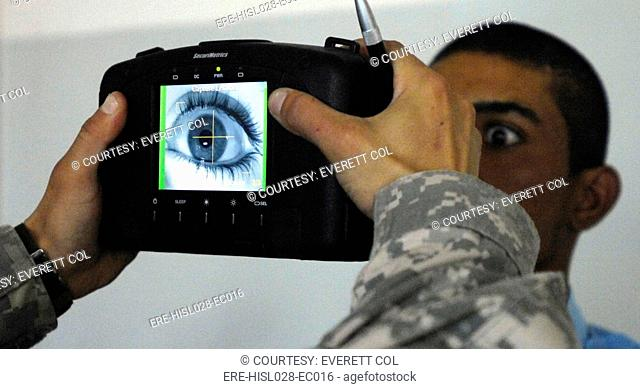 An Iraqi police recruit holds his eye open for a retinal scan administered by a US Soldier in Mahmudiyah Iraq May 30 2007. BSLOC-2011-12-288