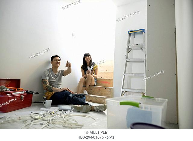 Couple drinking coffee discussing home improvement project