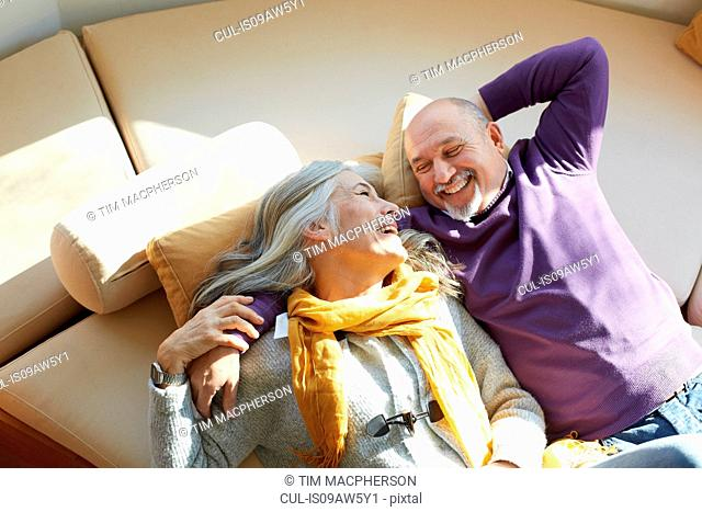 High angle view of mature couple lying on window seat face to face smiling