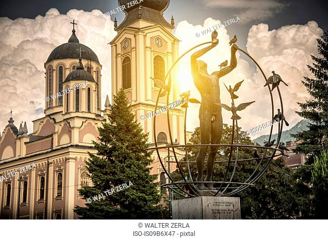 Multicultural Man Builds the World statue, Serbian Orthodox Cathedral in background, Liberation Square, Sarajevo, Bosnia and Herzegovina