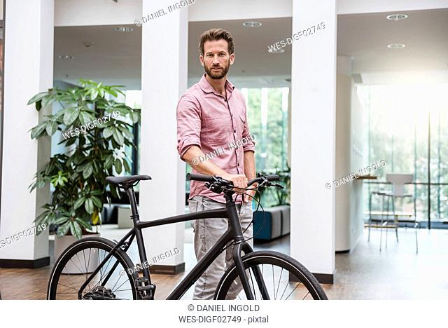 Portrait of man with bicycle in office