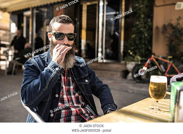 Portrait of bearded man wearing sunglasses smoking cigarette at outdoor gastronomy