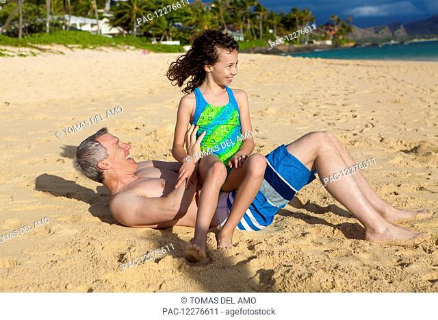 Father and daughter playing on a beach; Kailua, Island of Hawaii, Hawaii, United States of America