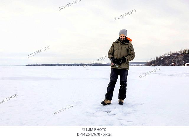 Man patiently waiting for a bite while ice fishing at Wabamun Lake; Wabamun, Alberta, Canada