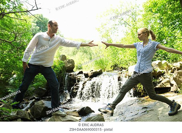 Couple hiking, woman reaching for man's hand