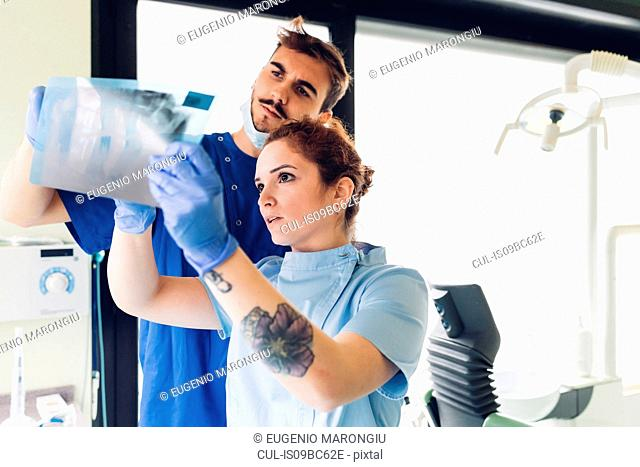 Two dentists in dentist office, looking at dental x-ray