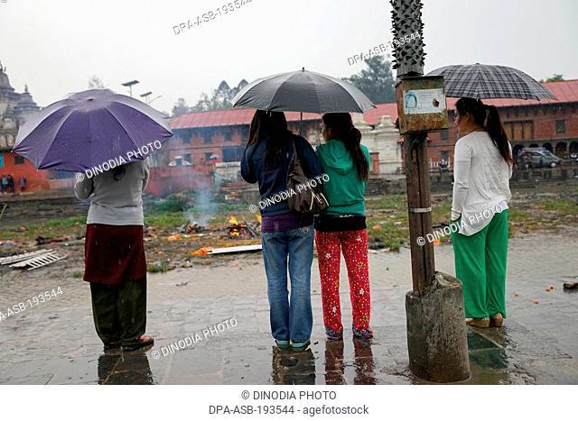 Women watching cremation, earthquake, kathmandu, nepal, asia