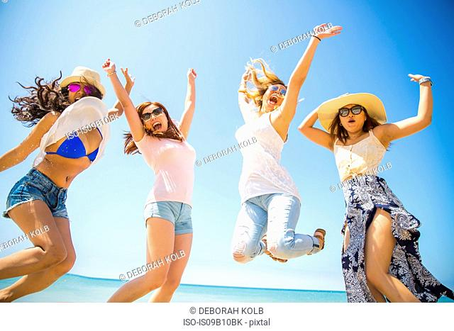 Four adult female friends jumping mid air on beach, Malibu, California, USA