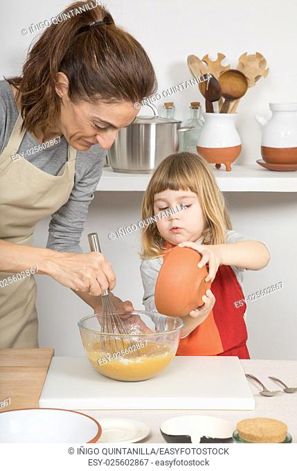 three years old child and woman, in teamwork, making and cooking a sponge cake at kitchen home, pouring flour in glass bowl and whipping with whisk