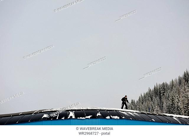 Man cleaning snow from rooftop