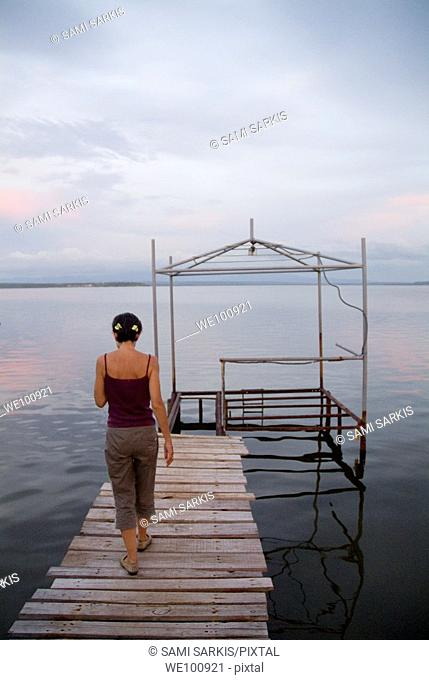 Woman walking on a wooden jetty at sunset, Punta Gorda, Cienfuegos Bay, Cuba