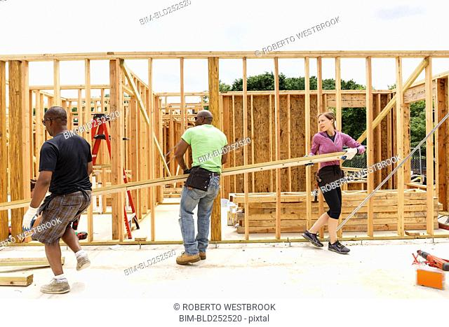 Volunteers carrying lumber at construction site