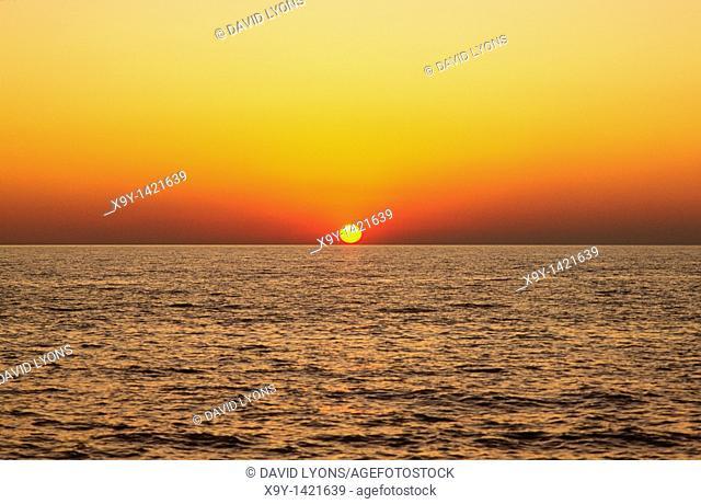 Sunset sunrise over ocean sea rising setting sun red