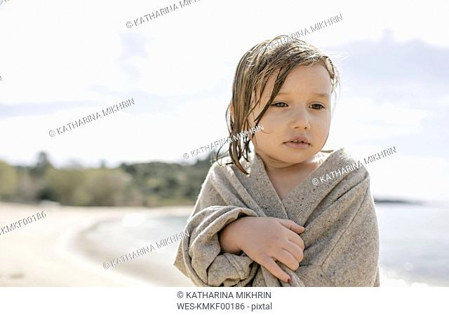 Portrait of sad little girl wrapped in cardigan