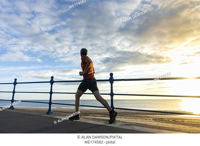 Seaton Carew, north east England, UK. Sixty year old jogger at sunrise as the sun rises over the North sea. Model released