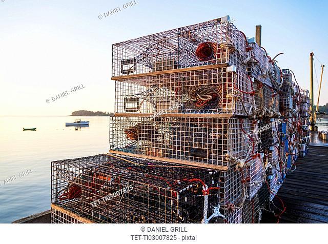 Stacks of lobster traps at sunrise
