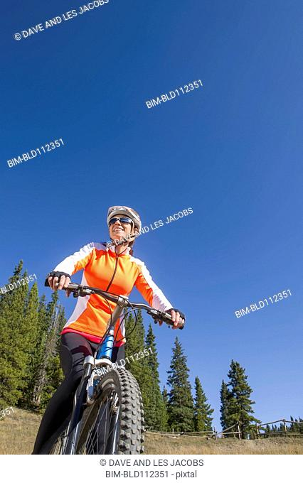 Hispanic woman riding dirt bike in rural landscape