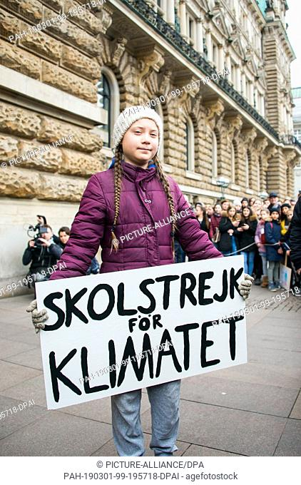 01 March 2019, Hamburg: Greta Thunberg, climate activist, stands with a banner in front of a rally on the town hall market in front of the town hall