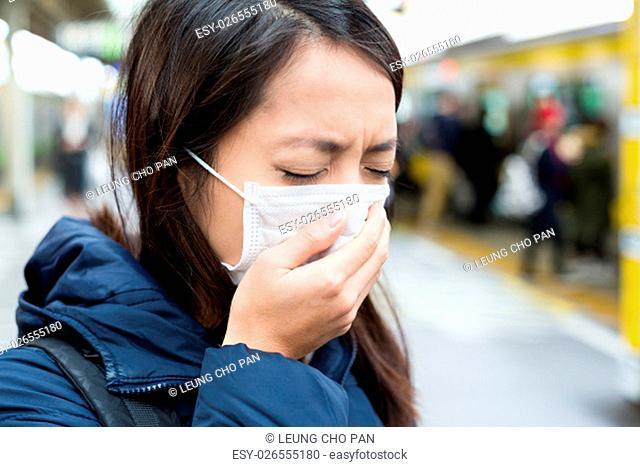 Asian woman wearing face mask at train station