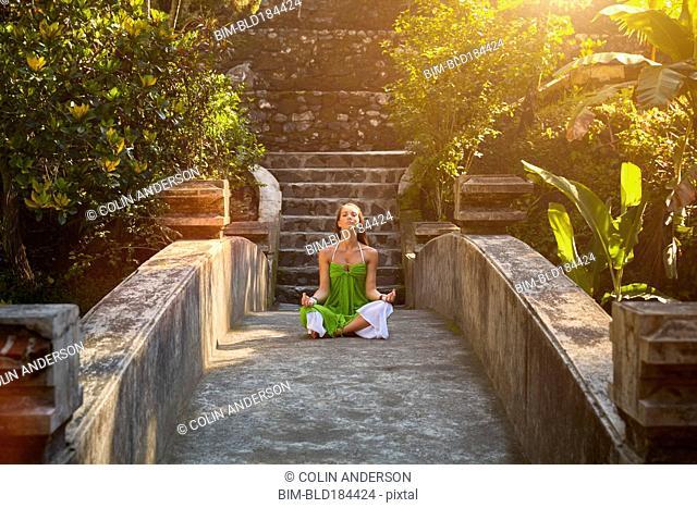 Pacific Islander woman meditating on walkway in jungle