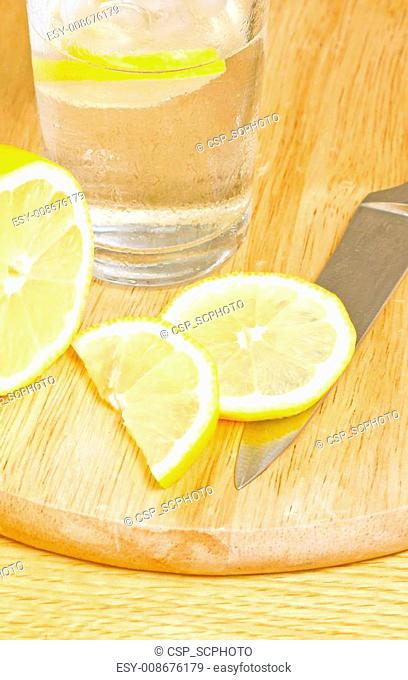 Iced water with lemon on chopping board