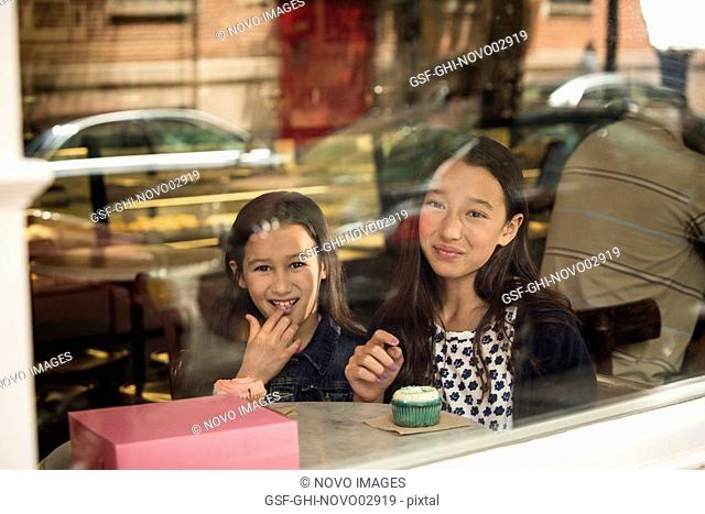 Two Young Girls Eating Cupcakes in Café Window