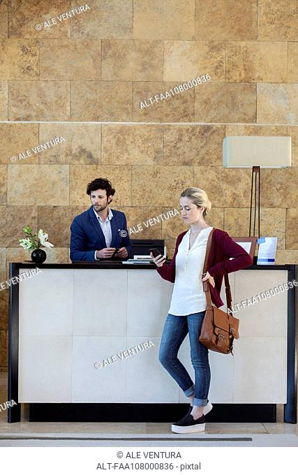 Woman looking at smartphone while waiting at reception desk