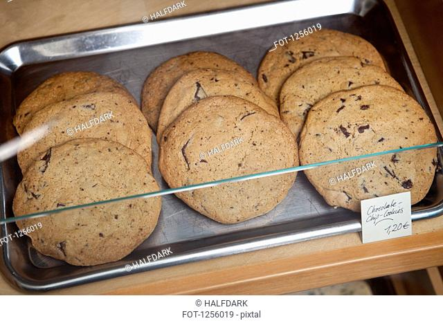 A tray of chocolate chip cookies in a display cabinet in a coffee shop