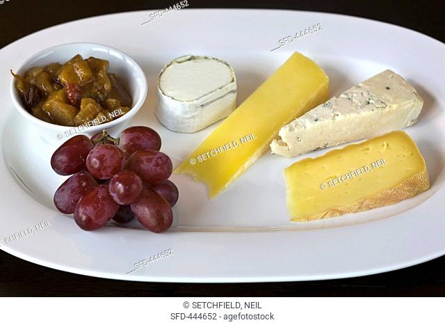 Cheese plate with grapes and pickles