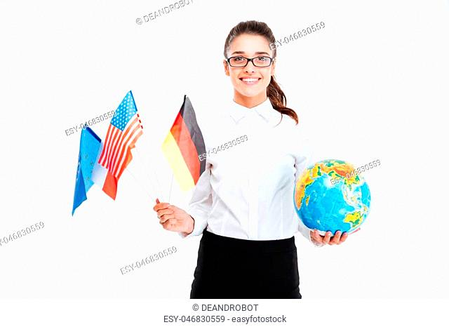 Smiling young businesswoman holding flags of countries and globe