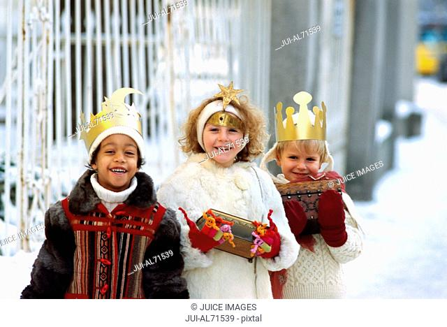Portrait of a three young children dressed as the Three Kings walking in the snow