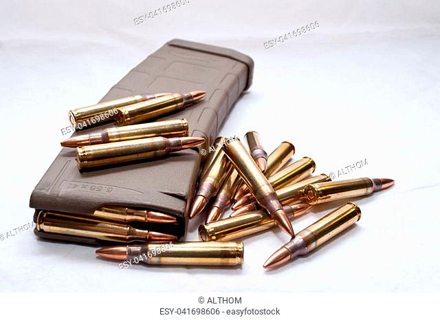 Several .223 caliber rounds and a loaded magazine on a white background