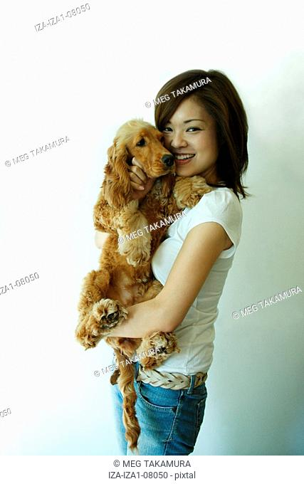 Young woman carrying a dog and smiling