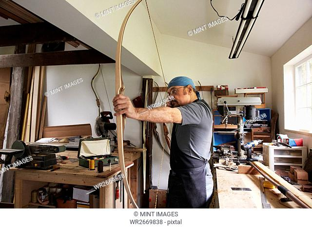 A man testing out a hand made bow by pulling the bow string