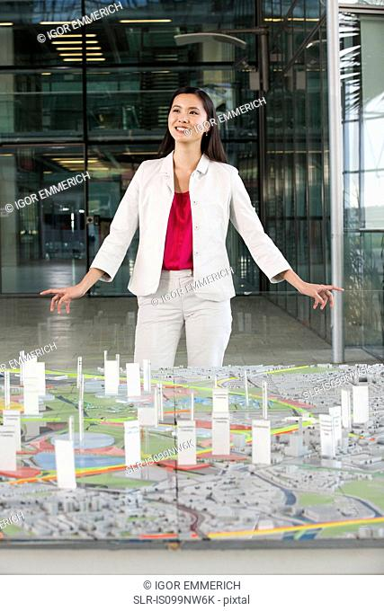 Young architect standing in front of model