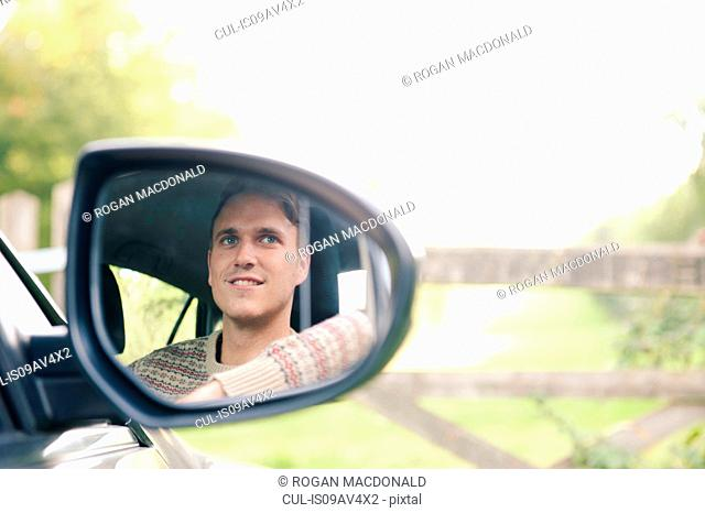 Wing mirror reflection of young man in car parked at rural gate