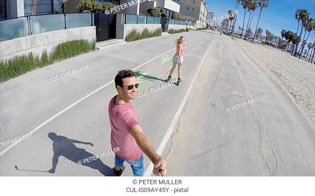 Rear view of rollerblading couple taking selfie, Venice Beach, California, USA