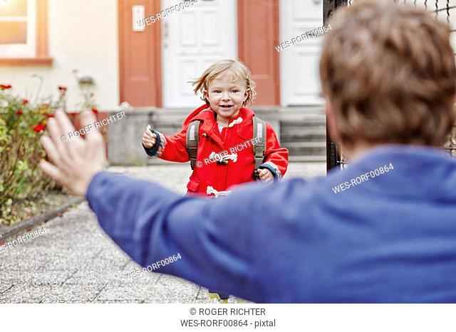 Happy daughter approacing father at house entrance