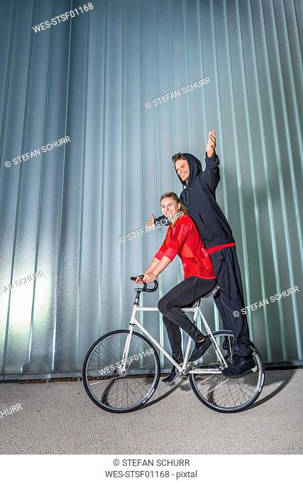 Young woman and man doing artistic cycling