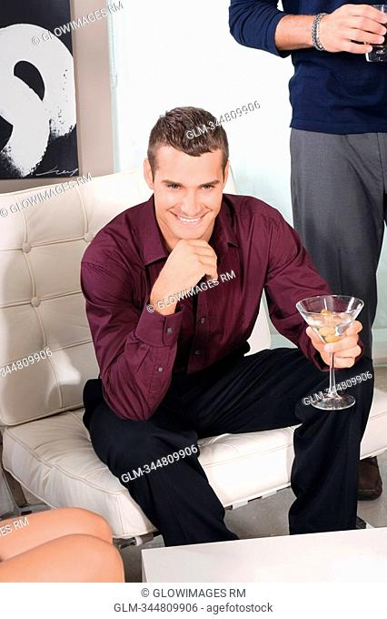 Young man holding a glass of martini and smiling