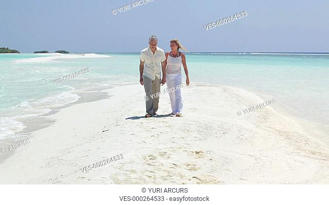 Mature couple walking hand in hand on a pristine beach on a summer,s day