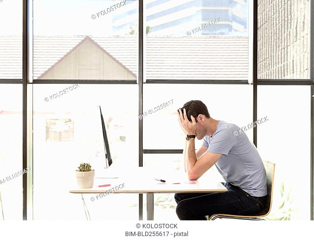 Frustrated Caucasian man with head in hands at desk
