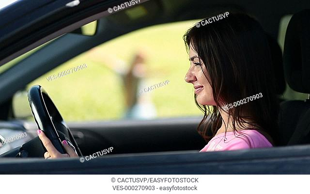 View through car window on woman standing in field