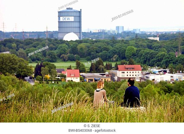 two people sitting on former waste disposal Deusenberg and enjoying the view to gas holder and Dortmund, Germany, North Rhine-Westphalia, Ruhr Area, Dortmund